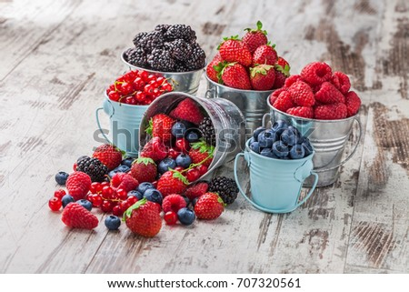 Berries mix blueberry, raspberry, red currant, strawberry, in five old tin cans spilled on white rustic wooden table in studio