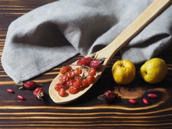 Berries  of the useful berberis plant, dry rose hips, viburnum in a wooden spoon and quince with a napkin on a dark on a wooden background, top view. Seasonal red barberry and yellow fruit for food