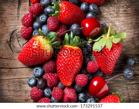 Berries on Wooden Background. Spring Organic Berry over Wood. Strawberries, Raspberries, Blueberry and Cherry. Agriculture, Gardening, Harvest Concept. Gardening. Vitamin. Diet