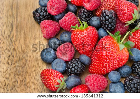 berries on wooden background (strawberries, raspberries, blackberries, blueberries) horizontal