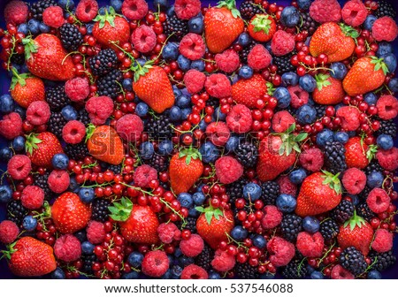 Berries overhead closeup colorful assorted mix of strawberry, blueberry, raspberry, blackberry, red currant in studio on dark background #537546088