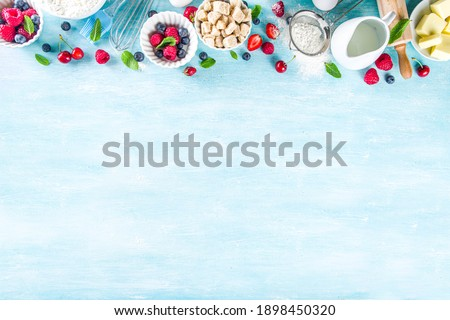 Berry cake baking recipe. Summer cooking baking background with assorted berries, baking ingredients, tools and utensils, light blue sun lighted wooden background flat lay top view copy space