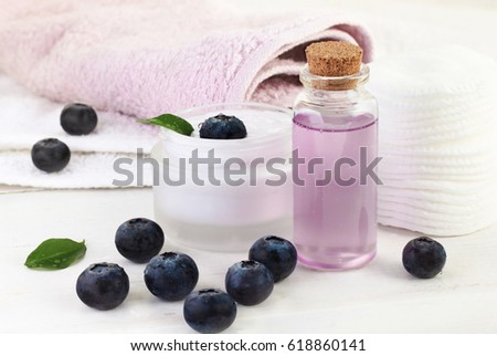 Berry extract cosmetic products. Lilac facial gel in glass bottle, blueberries, cream and towels