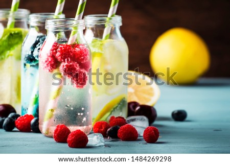Berry, fruit and citrus non-alcoholic cold beverages and cocktails in glass bottles on blue background, copy space #1484269298