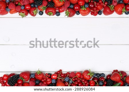Berry fruits frame with strawberries, blueberries, red currants, cherries, raspberries and copyspace
