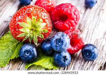 Berry fruits on wooden background or table. Blueberries, raspberries, strawberries, Forest fruits. Gardening ,agriculture,harvest and forest concept.