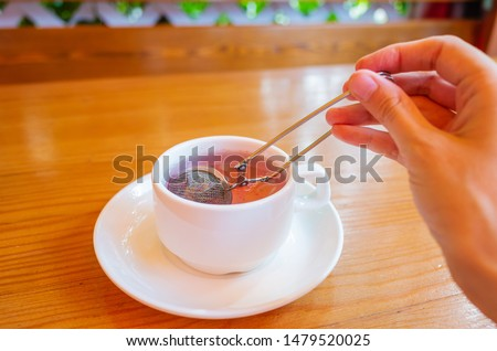 Berry herbal natural tea in a white cup on a wooden table. Tea strainer in a cup. Cozy minimalistic still life. Place for text. Healthy Food Concept. #1479520025