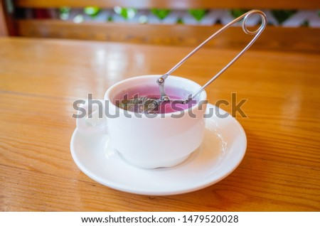 Berry herbal natural tea in a white cup on a wooden table. Tea strainer in a cup. Cozy minimalistic still life. Place for text. Healthy Food Concept. #1479520028