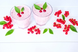berry milkshake and red currant berries on a white background close-up. cocktail of red currant berries in glasses on the table. background with milkshake and red currant berries.