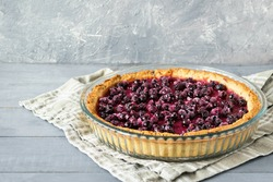 Berry pie, a tart filled with jam made from black currants, in glass form a gray background. Selective focus, close-up.