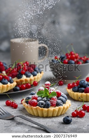 Berry tartlets with curd cream on a gray background. Summer fruit baking. Tartlets with raspberries, blueberries and red currants. Flying powdered sugar. Selective focus