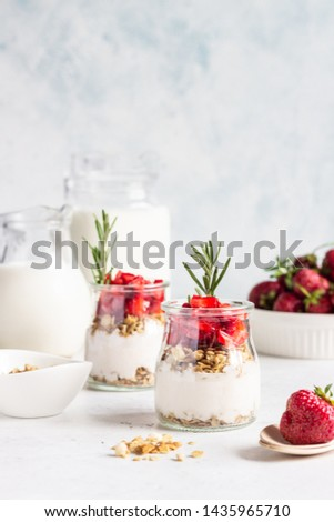 Berry yogurt with greek yogurt, fresh strawberries and granola in jars. Healthy breakfast parfait in glass cup. Copy space for text. #1435965710