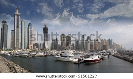 Berthing space in Dubai Marina, with several boat and yachts parked in front of the famous Marina district in Dubai, UAE.