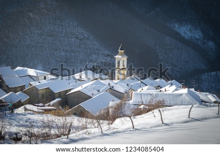 Bertone (Ottone), Piacenza, Italy - January 2013: Scenic winter view of picturesque quaint Italian village, church bell tower and fresh snow on rooftops. Photos with Snow #1234085404
