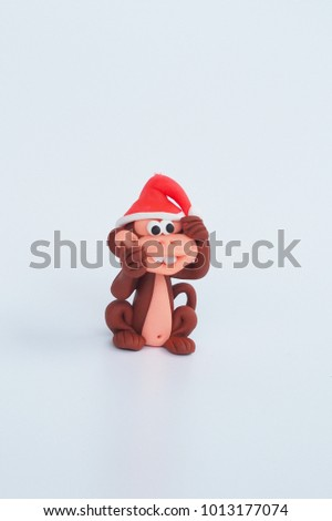 Beside of Small cute clay cartoon monkey handmade wear red Christmas hat and naughty funny face to tease on white background for kid , interior garden decoration , green rawmaterial