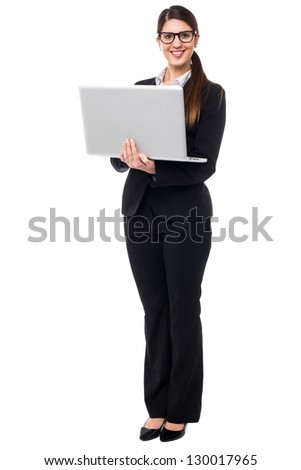 Bespectacled executive holding laptop. Full length portrait.