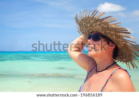 best aged woman on the beach with sun hat and sun glasses enjoys the sun