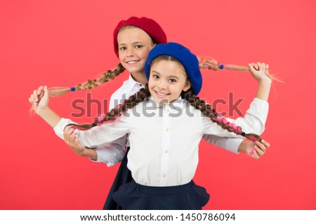 Best braided hairdo. Small girls being proud of long braid hairdo on pink background. Little kids holding plait hairdo. Children need new hairdo in hair salon.