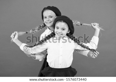 Best braided hairdo. Small girls being proud of long braid hairdo on pink background. Little kids holding plait hairdo. Children need new hairdo in hair salon.