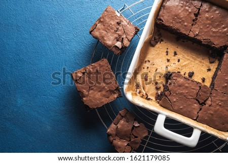 Photo of  Best brownies dessert in a white pan and on a cooling tray, on phantom blue table. Above view of freshly baked brownies. Delicious chocolate cake.