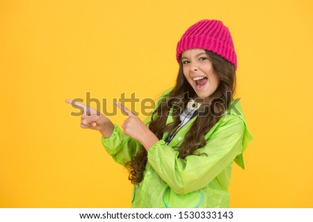 Best buy. Little girl point fingers at something yellow background. Happy child presenting product. Product promotion. Product advertising. Promoting product or service. Order and enjoy, copy space. #1530333143