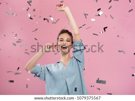 Best celebration. Cheerful optimistic girl is standing and exulting while raising her hands up with wide smile. Confetti are flying in air. Pink background