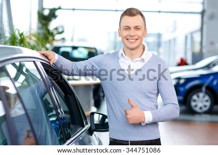 Best choice. Pleasant content handsome man standing near car and thumbing up while looking for an auto in autoshow