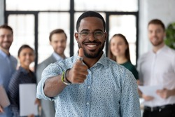 Best ever! Portrait of loyal excited black male client customer demonstrating thumb up sign recommending good product service, happy african employee looking at camera glad to work in company staff