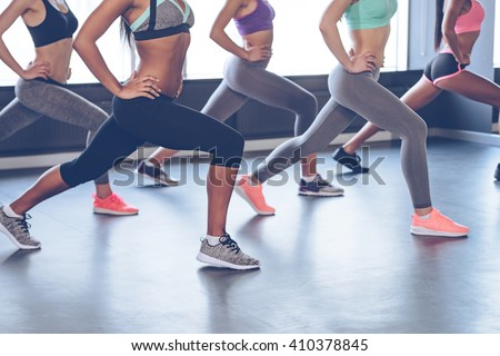 Best exercise for your booty. Side view part of young women with perfect buttocks in sportswear exercising while standing in front of window at gym