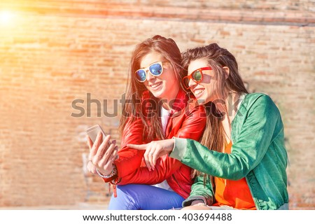 Best fashion addicted friends watching videos surprised on smartphone- Girlfriends having fun outdoors - Technology addiction concept - Main focus on right girl\'s face with artificial sunlight