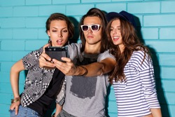Best friend hipsters wearing stylish bright outfits and having great time. Handsome boy with two beautiful ladies taking selfie self portrait pictures with film camera in front of blue brick.