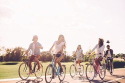 Best friends and road ahead. Group of young people riding bicycles along a road and looking happy