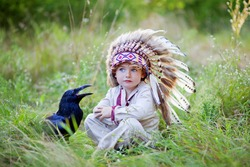 best friends, boy and his crow friend, the bird and the child against the backdrop of greenery, little boy and his pet in the summer park, sunny forest