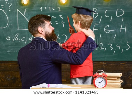 Best friends concept. Teacher with beard, father hugs little son in classroom while discussing, chalkboard on background. Child in graduate cap listening teacher, chalkboard on background, rear view. #1141321463
