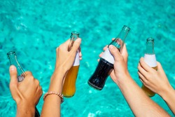 best friends drinking lemonade while refreshing in the swimmingpool hands close up on blue aquamarine color background