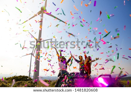 Best friends enjoying the outdoor party together with colorful papers in nature stock photo