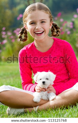 Best friends - happy girl with cute puppy in the garden