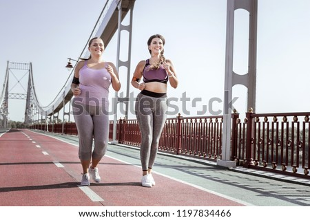 Best friends. Nice positive women smiling while jogging together on the bridge