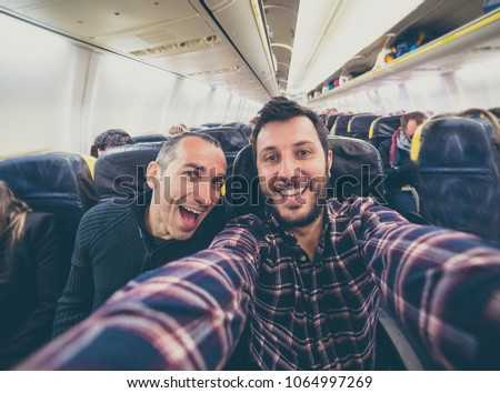 Best friends on the airplane ready to flight around the world. travel, holidays, vacation, happy people concept - smiling curious crazy guys traveler take selfie photo