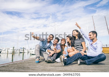 Best friends taking a self portrait - Group of young and happy people on vacation at harbor with sailing boats in the background