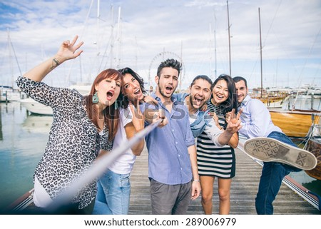 Best friends taking a self portrait with selfie stick - Group of young and happy people on vacation at harbor with sailing boats in the background