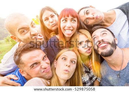 Best friends taking selfie outdoor with back lighting - Happy youth concept with young people having fun together - Cheer and friendship at picnic - Warm vivid filter with focus on redhead woman
