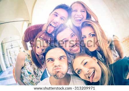 Best friends taking selfie outdoors with backlighting - Happy friendship concept with young people having fun together - Cold vintage filtered look with soft focus on faces due to sunshine halo flare