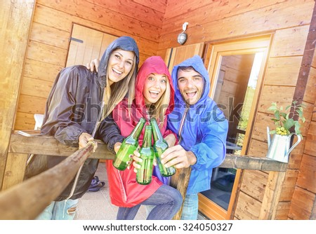 Best friends taking tilted selfie at camping bungalow with sunshine after the rain - Youth and freedom concept outdoors in autumn vacations - Young people having fun and cheering with bottled beer