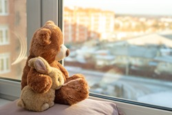 Best friends teddy bear and bunny toy sitting on window sill hugging each other and looking out of windows, sunlight, sunny day. Side view. Love, family and friendship concept. stay at home, safe.