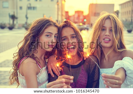 Best friends teen girls with sparklers at sunset in the city
