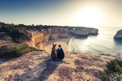Best friends travelers sitting at cliffs in Portugal at sunset.