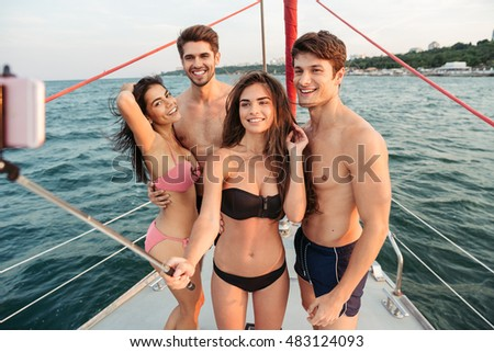 Best friends using selfie stick and taking pic on exclusive luxury sailing boat