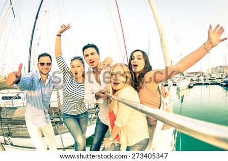 Best friends using selfie stick taking pic on exclusive luxury sailing boat party trip - Friendship travel concept with young people having fun together - Retro nostalgic desaturated color tone filter