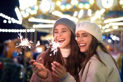 Best friends with sparklers on Christmas market